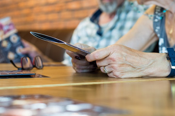 Close up an elderly woman hands holding cafe menu for dinner.