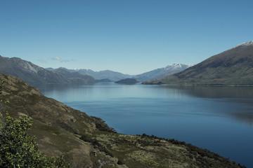 Aluminium Prints Reflection Paisaje de montañas frente a un gran lago donde se reflejan. Cielo azul despejado.
