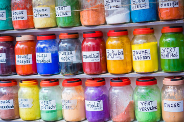 Assortment of glass jars on shelves in herbalist shop on a traditional Moroccan market (souk) in Essaouira, Morocco