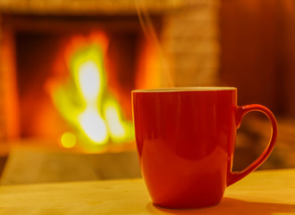 Mug  for  tea  or coffee , on background of cozy  fireplace, soft  focus.