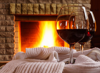 Glasses  of  red wine before cozy fireplace.