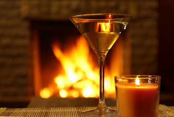 Martini glass and christmas candle under fireplace background.