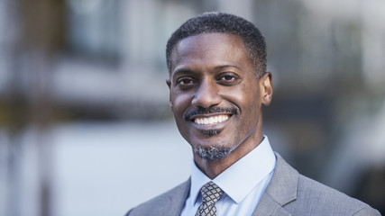 Portrait of positive handsome black professional smiling to camera