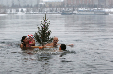 Members of the Cryophile amateurs winter swimmers club swim with a Christmas tree in Krasnoyarsk