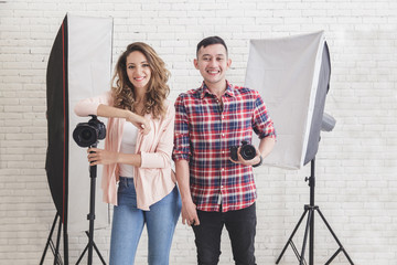 two young photographer in studio with lighting at the background