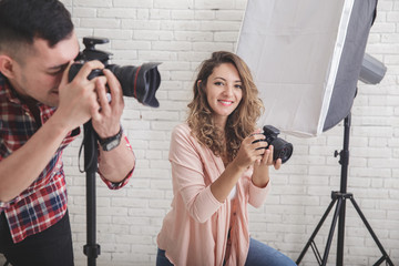 young female photographer looking at camera, while her partner t