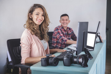 two photographers smiling while editing photos in their computer