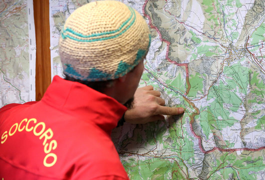 An Alpine and Speleological Aid volunteer shows the map before a training near French border where migrants try to cross from Italy to France, in Bardonecchia