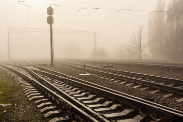 Railroad tracks in the fog on autumn