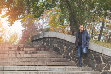 Handsome man walking in the autumn park