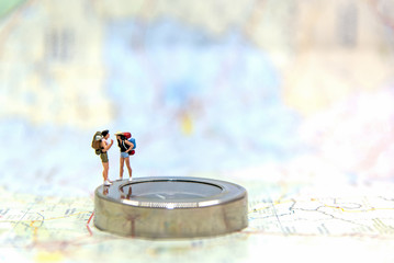 Miniature Group traveler with backpack standing on wold map for travel around the world.  Travel Concept