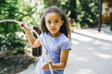 Girl playing with stick in forest