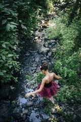 Girl in ballet dress walking in creek in the forest