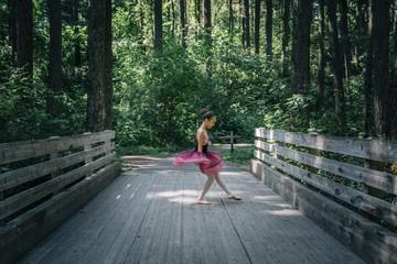 Girl in ballerina costume dancing on bridge in forest