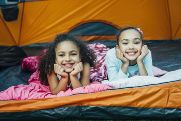 Smiling sisters in sleeping bags in tent