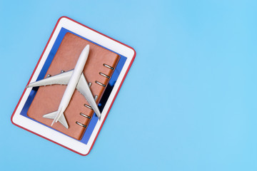 Toy plane on Notebook and Tablet on blue copy space