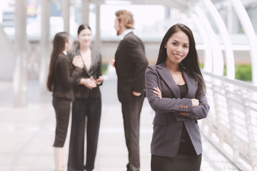 Confident looking mixed race business woman posing arm cross.