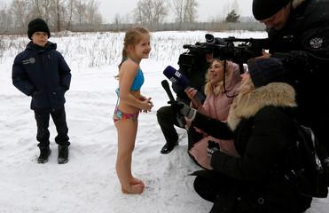 Journalists interview a girl after bathing in the Yenisei River in Krasnoyarsk