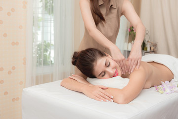 Asian exotic holiday spa concept. Beautiful young white woman enjoy relaxing during massage at spa, taken indoor in real spa location.