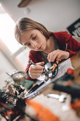 Wall Mural - Girl building a robot at home