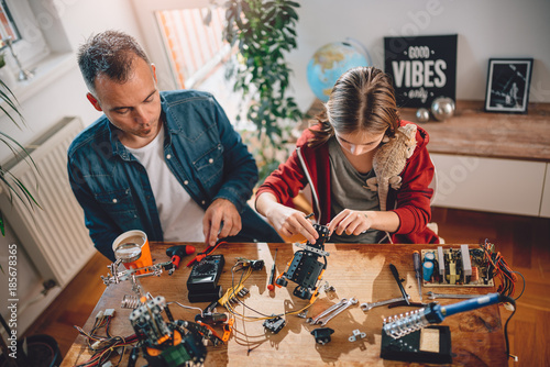 Wall mural Father and daughter building robot
