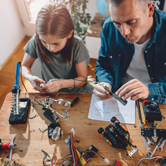Wall Mural - Father and Father and daughter working on electronics components building robot