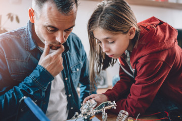Wall Mural - Father and daughter looking at electronic schematics