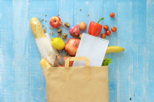 Paper bag different fresh health food notebook on wooden background