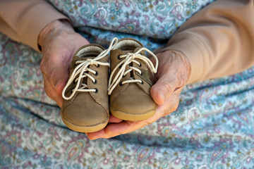 Grandmamma holding baby shoes in her hands