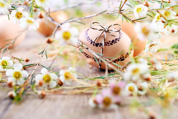 Painted Easter egg on wood with white flowers and hay around