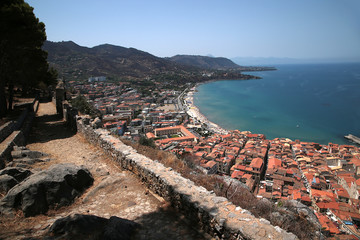 Cefalu, Sicily, Italy. Ruins of fortifications on the rock of La Roca and view of the city on the coast