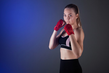Female boxer makes a fight with a shadow, dark background with space for text. Strong and confident, she will be a champion.