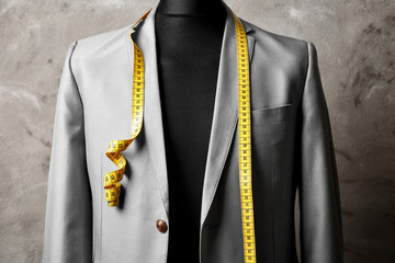 Custom-made suit on mannequin against grey background