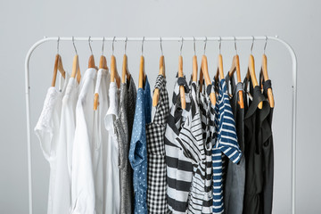 Stylish clothes hanging on wardrobe stand against light background