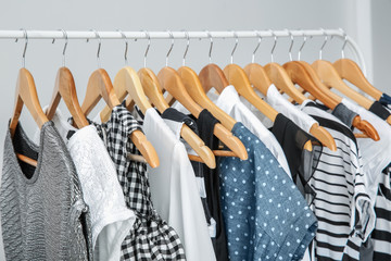 Wall Mural - Stylish clothes hanging on wardrobe stand against light background