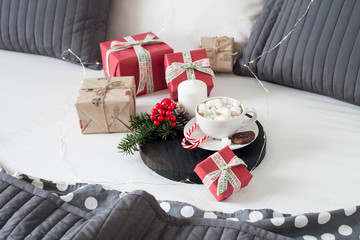 Christmas Breakfast in bed with a Cup of Coffee gift boxes, garlands and Christmas composition.