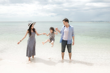 Young family on beach holding each other. Young happy interracial family on beach hugging together. Asian woman, Caucasian man, young girl. Young mixed race family concept.
