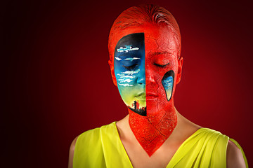 Woman with creative makeup, portrait, face, shoulders. Against the background of the red black studio, sleep, hallucinations, surrealism. Crazy art concept new idea. Part of face landscape, nice view