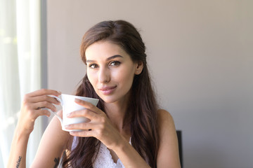 Woman having coffee and smile. Beautiful white woman having her morning coffee and smile looking very happy.