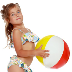 Little girl in a swimsuit with a ball