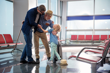 Family embrace. Full length of positive mature father with gray-haired grandfather and little girl are standing at airport lounge and hugging. They are expressing happiness. Copy space in right side
