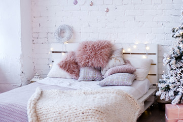 bed made from pallets with fluffy pink pillows