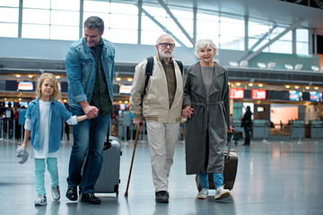 Full length of delighted old grandparents are going with their son and granddaughter at airport terminal to check-in on their flight. They are carrying suitcases and expressing happiness