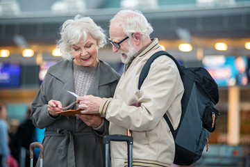 What time our plane. Involved gray-haired couple is standing at airport terminal and holding flight tickets. They are checking travel documents while discussing together with smile