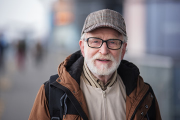 Old generation. Portrait of positive senior bearded man with glasses is standing outdoors and looking at camera with slight smile