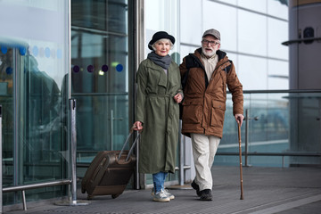 Arrival. Full length portrait of pleasant positive senior man with cane and woman with suitcase are standing together near airport building. They are looking at camera with slight smile