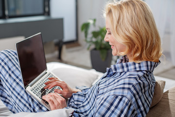 Time to communicate. Side view profile of smiling girl using laptop at home. She is typing with joy