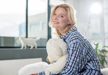 Joyful woman sitting and holding close teddy toy. She is looking at camera with smile. Copy space in left side