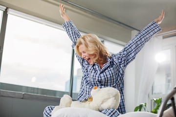 Low angle of cheerful woman sitting on cozy bed. She is yawning