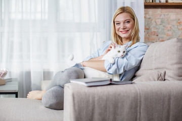 Full length portrait of tranquil lady resting in sitting room. She is holding white fluffy cat and smiling at camera. Copy space in left side